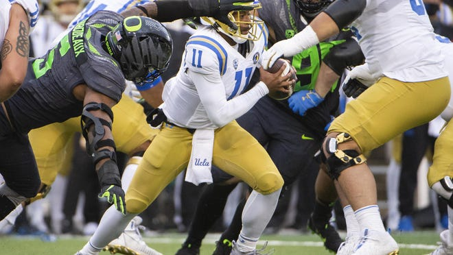 UCLA quarterback Chase Griffin slips past Oregon  defensive end Kayvon Thibodeaux during Oregon's 38-35 win Saturday. The former Hutto star completed 19 of 31 passes for 195 yards and a touchdown in his first collegiate start.