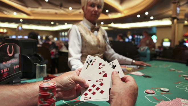 A player looks through his hand after being dealt cards by a dealer during a game of Pai Gow Poker at the Horseshoe Southern Indiana casino in 2009.