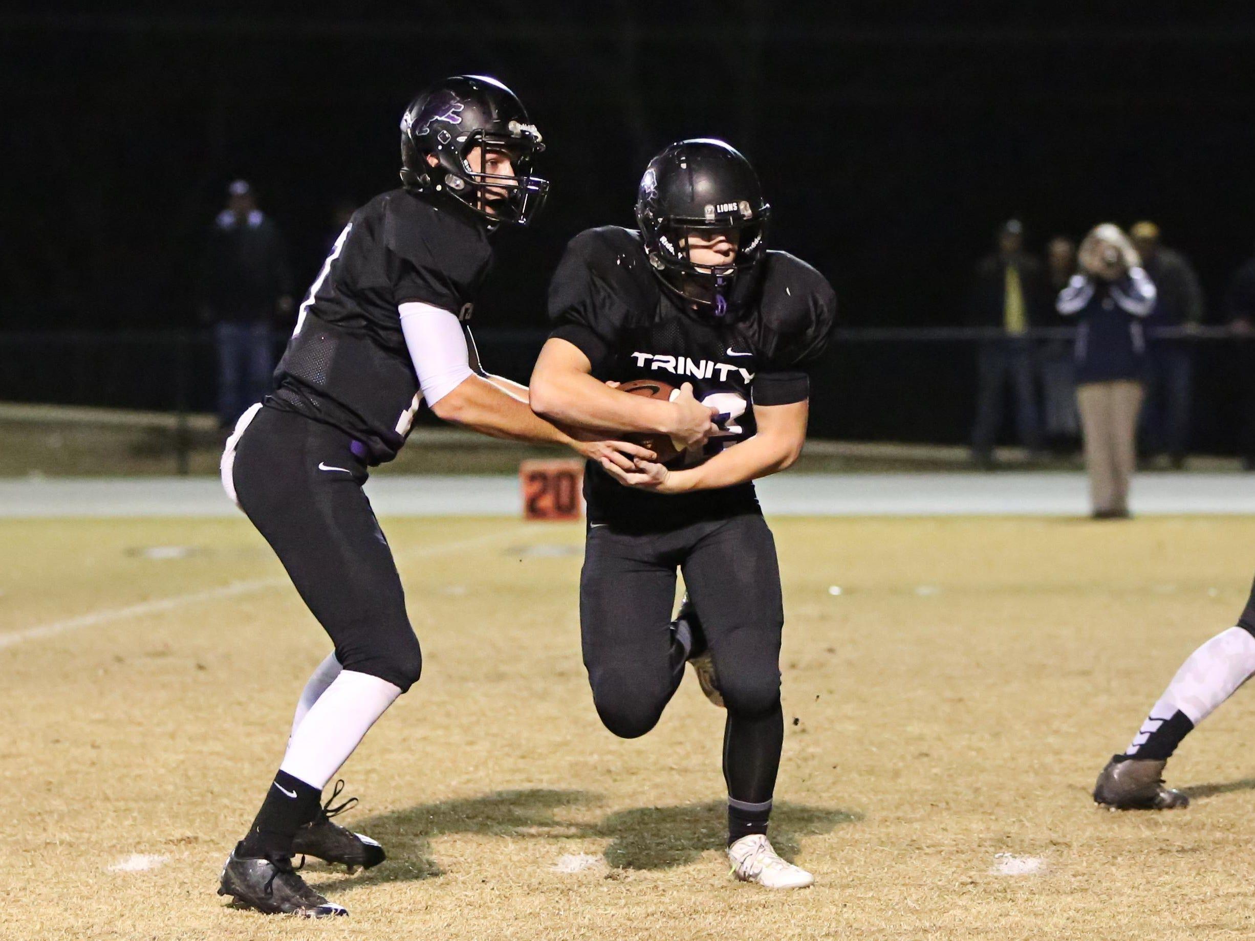 Trinity quarterback Tristan Bonstetter fakes the handoff to Greyson Long in Friday's Class 2A semifinal game vs. Trezevant.