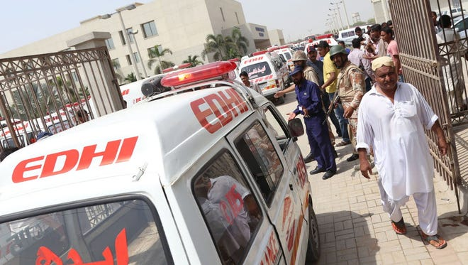 Ambulances carry the bodies of victims who were killed when unknown assailants opened fire at a bus carrying members of Ismaili Shia community in Karachi on May 13.