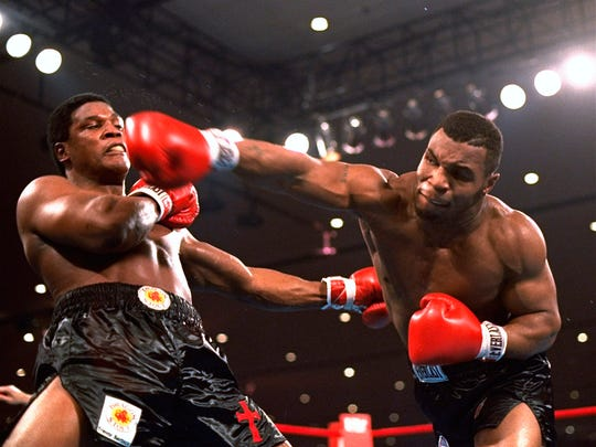 FILE - In this Nov. 22, 1986, file photo, Mike Tyson, right, delivers a blow to Trevor Berbick during a boxing bout in Las Vegas. Tyson hasn't announced any plans to return to the ring, though he did suggest on an Instagram post he might make himself available for 3 or 4-round exhibitions if the price was right. And already some people in Australia are talking about offering him $1 million to fight an exhibition against a rugby star or two. (AP Photo/Douglas C. Pizac, File)