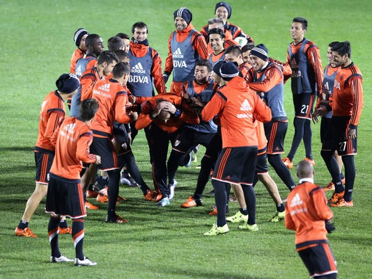 Argentine club River Plate's players share a light moment during the team's practice session for their match against Sanfrecce Hiroshima at the FIFA Club World Cup soccer tournament in Osaka, western Japan, Monday, Dec. 14, 2015. (AP Photo/Eugene Hoshiko)