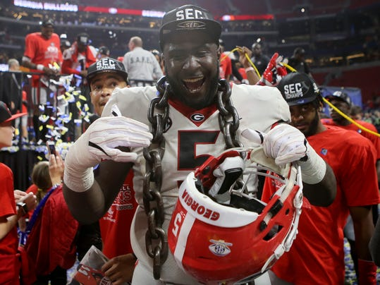 Georgia defensive lineman Julian Rochester celebrates after making his way off the stage after Georgia defeated Auburn 28-7 during the Southeastern Conference championship NCAA college football game Saturday, Dec. 2, 2017, in Atlanta, Ga. (C.B. Schmelter/Chattanooga Times Free Press via AP)