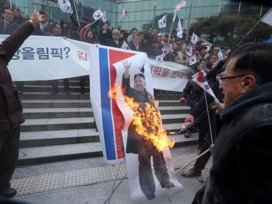 South Korean protesters burn a portrait of North Korean