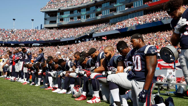 In this Sept. 24, 2017 file photo, several New England Patriots players kneel during the national anthem before an NFL football game against the Houston Texans in Foxborough, Mass.  Patriots fans have burned team gear in protest after a number of players kneeled during the national anthem before last weekend's game. More than 100 people came out to Swansea, Massachusetts, on Thursday, Sept. 28 to throw Patriots T-shirts and other team apparel into a fire pit as they waved American flags and sang patriotic songs. (AP Photo/Michael Dwyer, File)