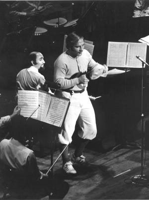 """Johnny Bench narrates """"Casey at the Bat,"""" to original music by Frank Proto, at the piano, shown here in the world premiere performance with the Cincinnati Pops Orchestra in Music Hall in 1973."""