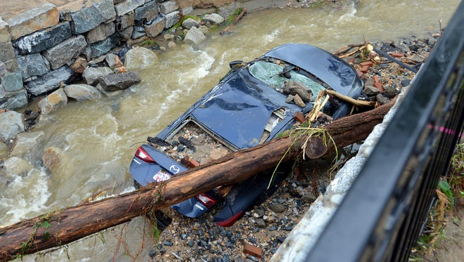 Water moves past a car swept into the riverbank and smashed by a fallen tree is shown just off Main Street in flood-ravaged Ellicott City, Md., May 28, 2018.