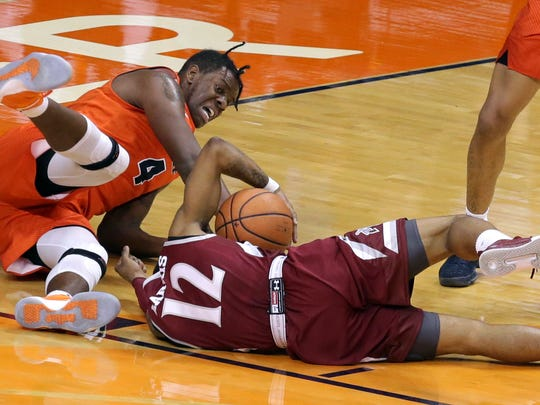 UTEP's Tirus Smith dives on NMSU's AJ Harris as they scuffle for a loose ball Thursday at the Don. NMSU defeated UTEP 80-60