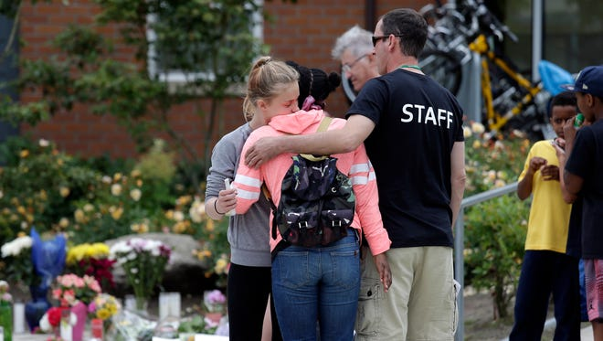 Zamirah Cacho, center, is embraced by Mykla Gainey, left, and a staff member from a nearby community center at a memorial outside the place where a pregnant mother was shot and killed a day earlier by police on June 19, 2017, in Seattle.