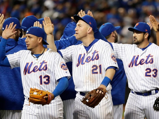New York Mets' Asdrubal Cabrera (13), Todd Frazier (21) and Adrian Gonzalez (23) celebrate with teammates after a baseball game against the Milwaukee Brewers, Friday, April 13, 2018, in New York.
