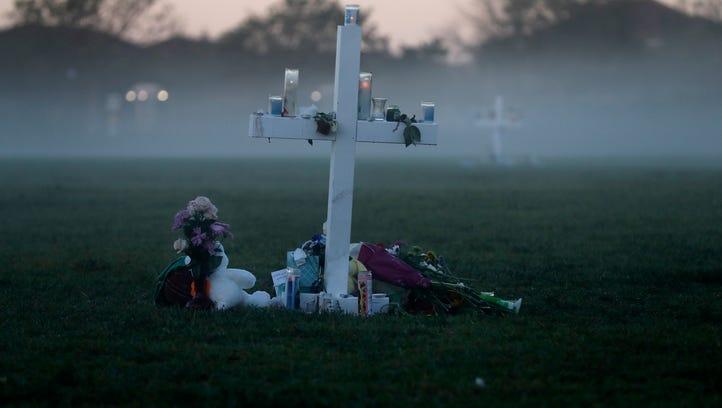 An early morning fog rises where 17 memorial crosses