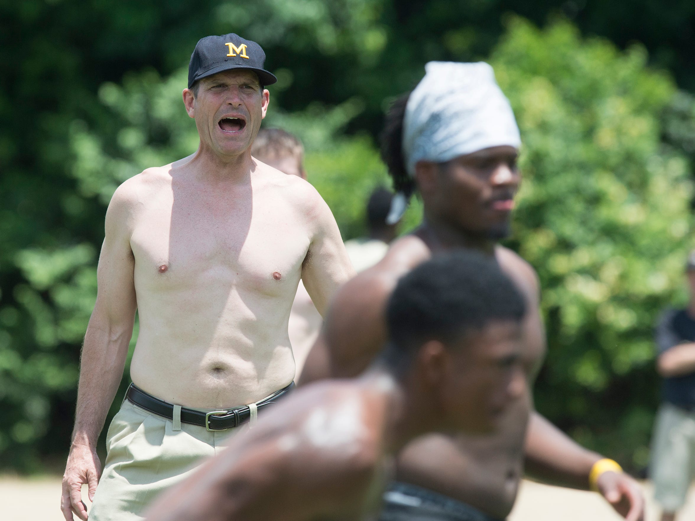 June 5, 2015: Michigan football coach Jim Harbaugh plays shirtless with participants during the Coach Jim Harbaugh's Elite Summer Football Camp at Prattville High School in Prattville, Ala.