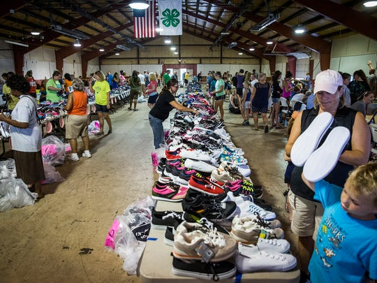 Shoes sorted by volunteers line a table during Tools