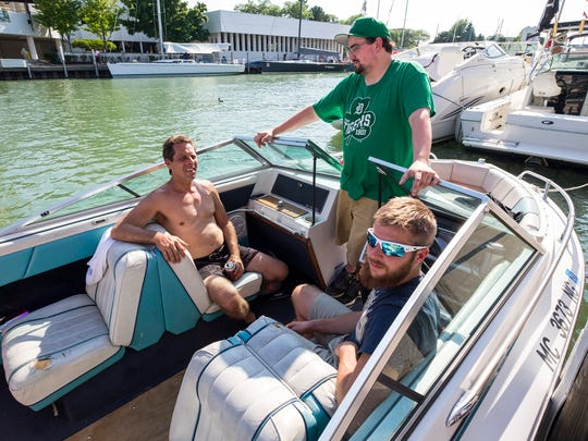 Rich Macumber, left, and his son Rich, right, hang out on a boat with their friend Ian Lynch on Boat Night Friday, July 13, 2018, during Boat Week in Port Huron.