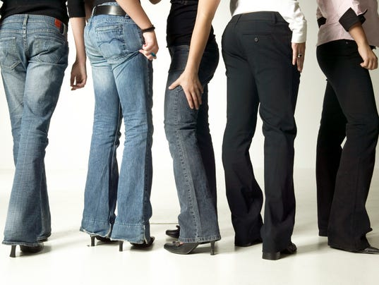 Women wearing denim jeans, posing in studio, low section