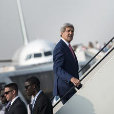 U.S. Secretary of State John Kerry boards his plane at Cairo International Airport on September 13.