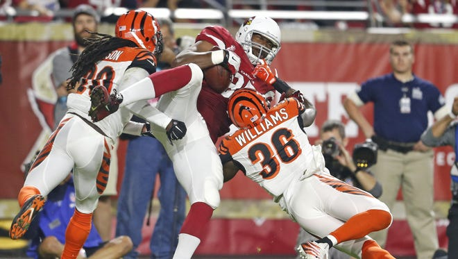 Cardinals' Darren Fells (85) makes a touchdown grab over Bengals' Shawn Williams (36) and Reggie Nelson (20) in the first half on Nov. 22, 2015 in Glendale, Ariz.