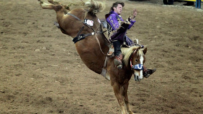 Tilden Hooper competes in bareback riding during the fourth round at the National Finals Rodeo at the Thomas & Mack Center in Las Vegas on Sunday, Dec. 7, 2014. (AP Photo/Las Vegas Review-Journal, Erik Verduzco)