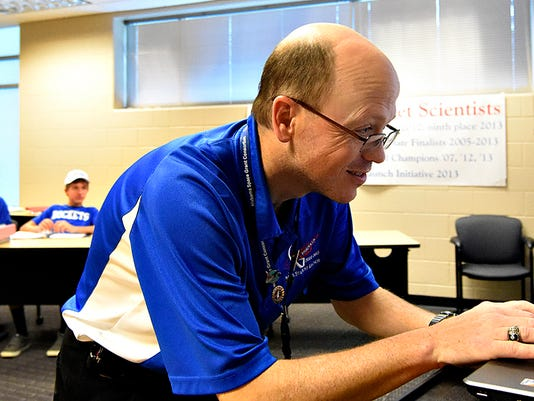 Physics Teacher Brian Hastings, front, prepares for a teleconference between Spring Grove Area High School Rocketry Team students, at back,  and NASA, as they kick off the 2016 NASA Student Launch Initiative (SLI) program at Spring Grove High School in Spring Grove, Pa. on Wednesday, Oct. 7, 2015. There are 14 high school teams involved in the program from across the country, two of which are from Spring Grove, and are the only Pennsylvania teams to have been selected. The teams will need to raise $25,000 dollars to fund their projects, through multiple fundraising events. Dawn J. Sagert - dsagert@yorkdispatch.com