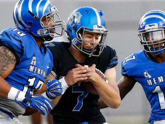 April 22, 2016 - University of Memphis quarterback Brady Davis (middle) is stopped by defenders DeMarco Montgomery (left) and Chris Morley (right) during the Friday Night Stripes spring game. (Mark Weber/The Commercial Appeal)