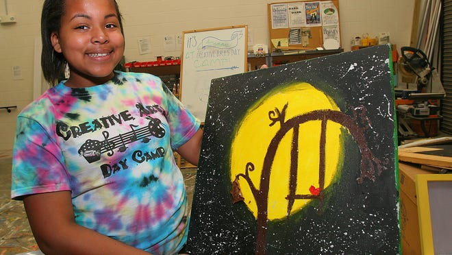 Celina Williams shows her painting from Creative Art Camp.