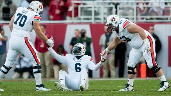 Auburn quarterback Jeremy Johnson (6) gets help up after being sacked by Alabama during the Iron Bowl at Bryant Denny Stadium in Tuscaloosa, Ala. on Saturday November 26, 2016. (Mickey Welsh / Montgomery Advertiser)