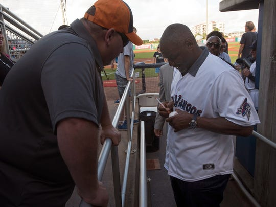 NFL Hall of Famer, Derrick Brooks, left, signs an autograph for a Blue Wahoos fan after joining the Wahoos ownership group, Wednesday, May 23, 2018, Brooks joins Bubba Watson as minority owners of Studer's minor league baseball team.
