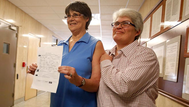 Angela Channell, right, and Dawn Hicks, left, show  their marriage license Feb. 13, 2015, to friends and supporters. They were the first gay couple to receive a marriage license from Tuscaloosa County.