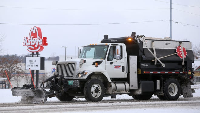 A Tennessee Department of Transportation truck clears the Highway 45 Bypass near Union University Drive in Jackson, Tenn., on Friday, Jan. 6, 2017.