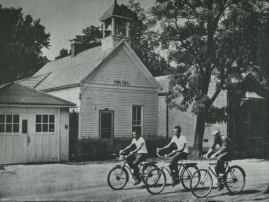 Boys ride bicycles in the 1960s  past the Pewee Valley