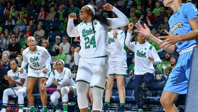 Notre Dame Fighting Irish guard Arike Ogunbowale (24) celebrates after a basket and a foul by Marquette Golden Eagles guard Natisha Hiedeman (5) in the overtime period at the Purcell Pavilion.