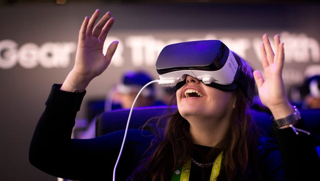 A woman reacts as she uses a new Samsung Gear 360, a 360-degree camera, at the Mobile World Congress.