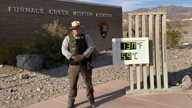 A national park ranger stands in front of the thermometer at Furnace Creek Visitor Center. The Celsius display should read 54 degrees.