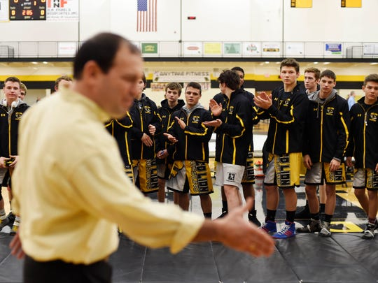 Biff Walizer, who coached varsity wrestling from 1999-2011, is clapped into the gym by current wrestlers during a celebration honoring the 50th anniversary of the Red Lion wrestling program on Wednesday. Past coaches and wrestlers were honored at the celebration before the varsity match.