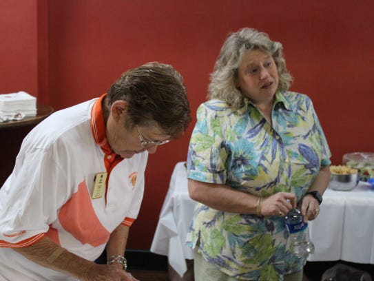 Ann Young and Annette Pulley speak to guests and prepare