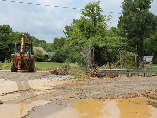 Crews work to clear debris from a ditch and repair