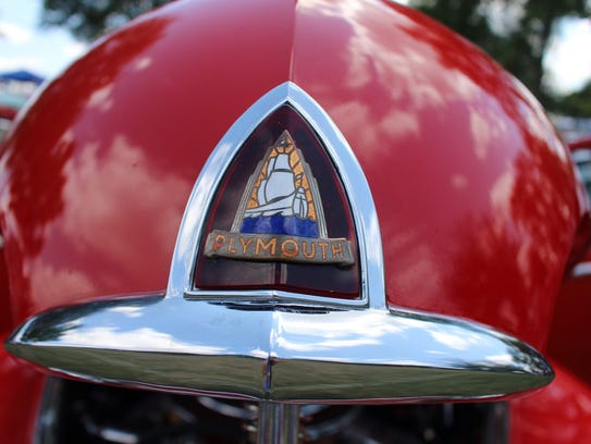 The vintage Plymouth had a stained glass-like emblem.