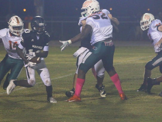 Dunbar's Rocky Jacques-Louis (14) and Derrick Hunter (52) close in on a Mariner ball carrier during a game on Oct. 20.