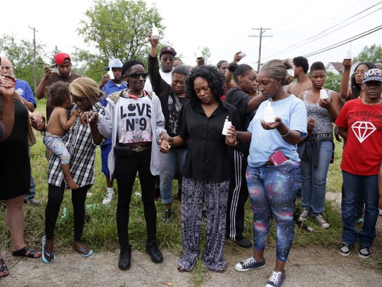 Alisha Jackson is surrounded during a vigil held by