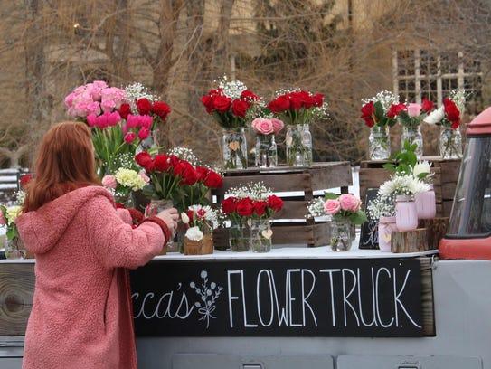 Alexa Hess arranges flowers for sale on her truck.