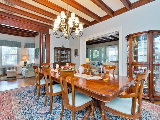 The  dining room features decorative molding and beamed high ceilings.