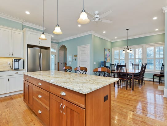 The modern kitchen features an expansive granite stone center island with countertops and stainless steel appliances.