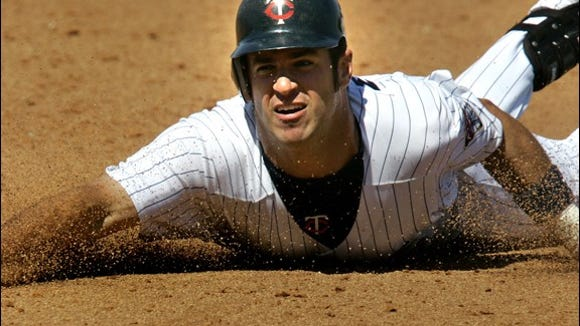 Minnesota Twins' Joe Mauer slides into third head first on a triple in the sixth inning against the Tampa Bay Devil Rays in Fort Myers., Fla., Sunday, March 26, 2006. (AP Photo/Charles Krupa)