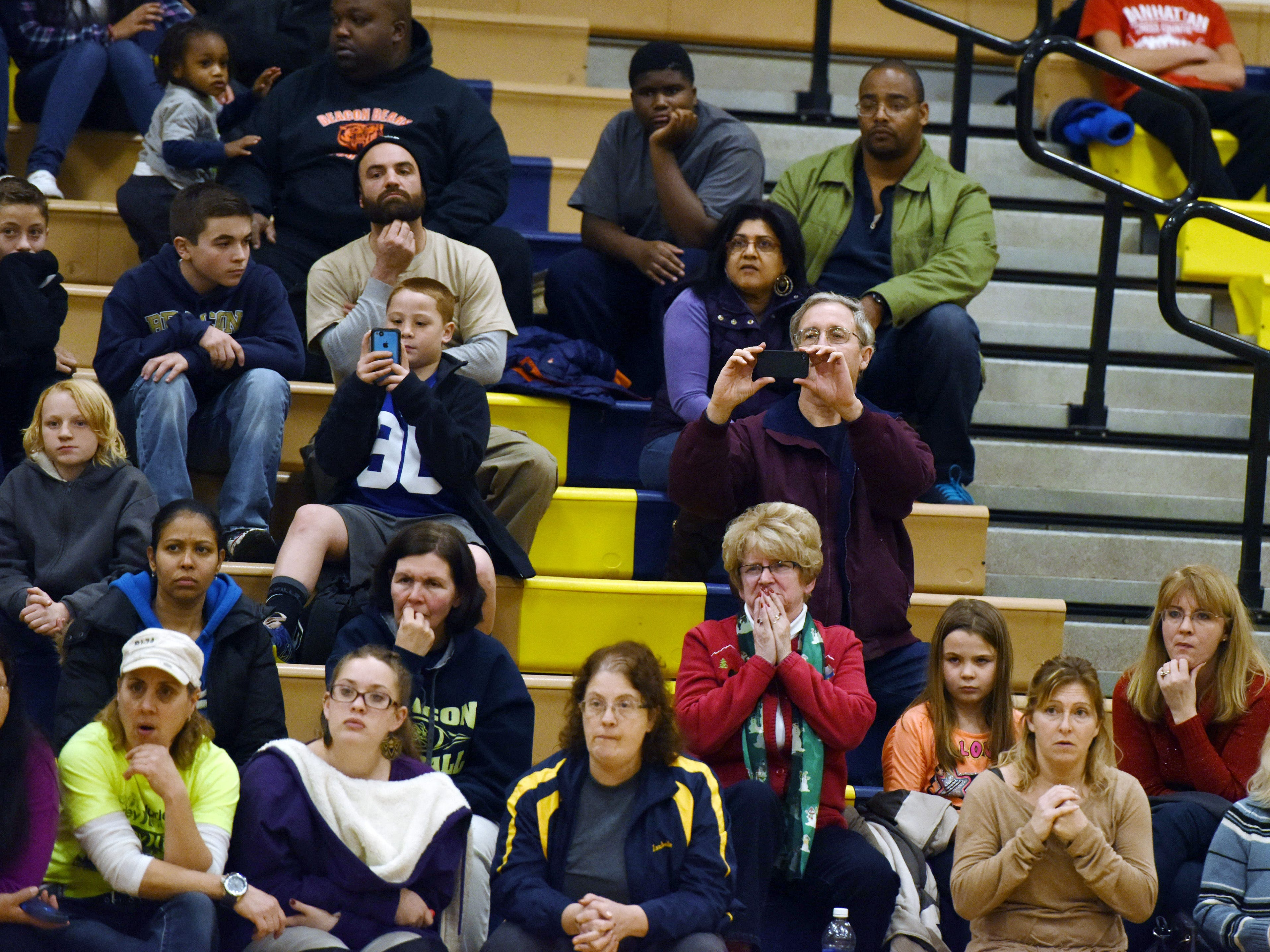 John Ollive, father of Beacon High School wrestler Liam Ollive, center right, watches and records his son wrestle in Beacon in December.