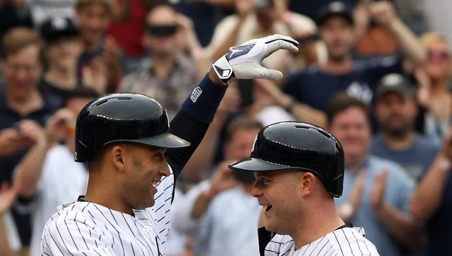 Derek Jeter and Brian McCann rejoice after McCann's home run, one of two he hit Sunday.