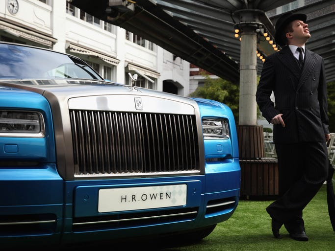 An actor poses besides a Rolls Royce Waterspeed Phantom Drophead Coupe at the Bluebird Cafe in London