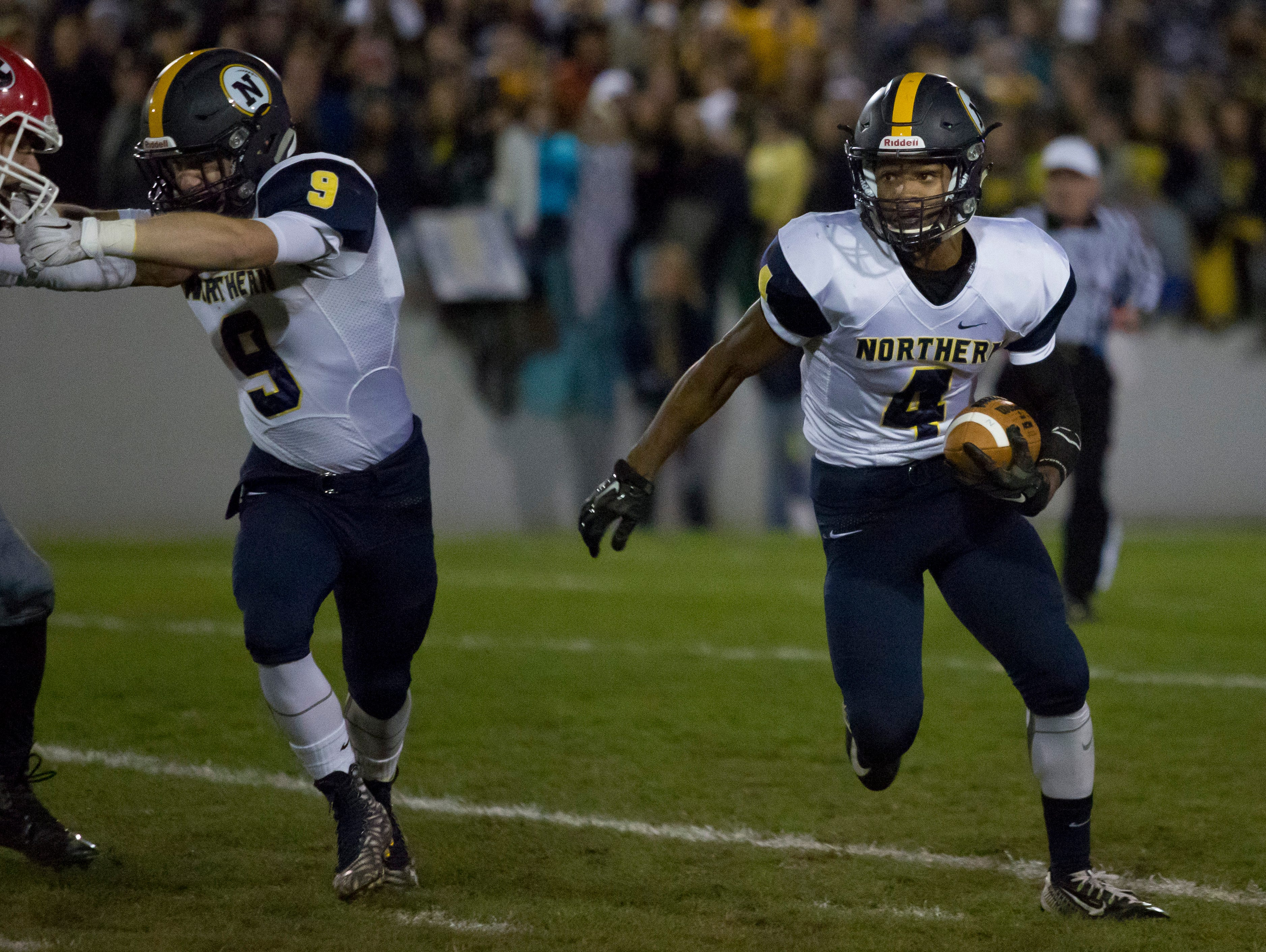 Port Huron Northern sophomore Steve Mason runs the ball as senior Adam Shier clears the way during the Crosstown Showdown Friday, October 23, 2015 at Memorial Stadium in Port Huron.