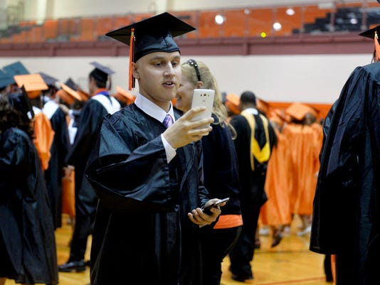 Central York graduate Peter Falci takes a photo for two fellow graduates before commencement in June.