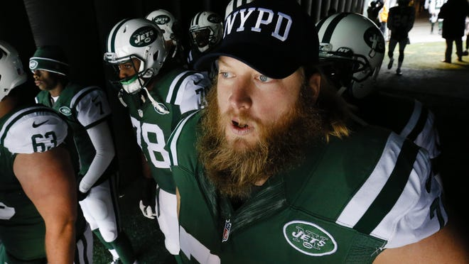 New York Jets center Nick Mangold wears an NYPD hat as he waits to go on the field for the start of an NFL football game against the New England Patriots, Sunday, Dec. 21, 2014, in East Rutherford, N.J.