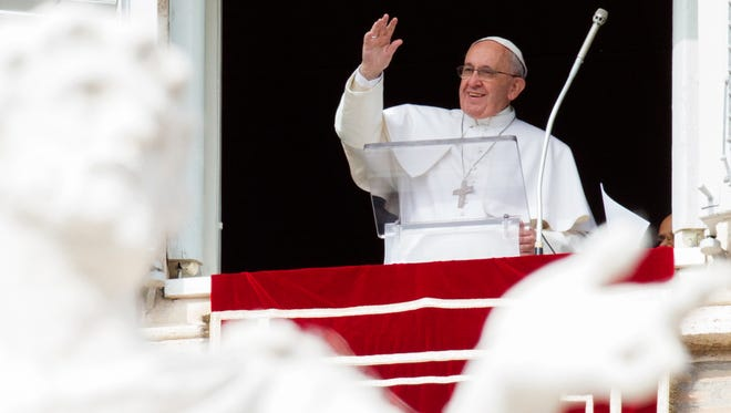 Pope Francis waves to the faithful from his studio window overlooking St. Peter's Square during the Angelus noon prayers at the Vatican on Feb. 22, 2015.
